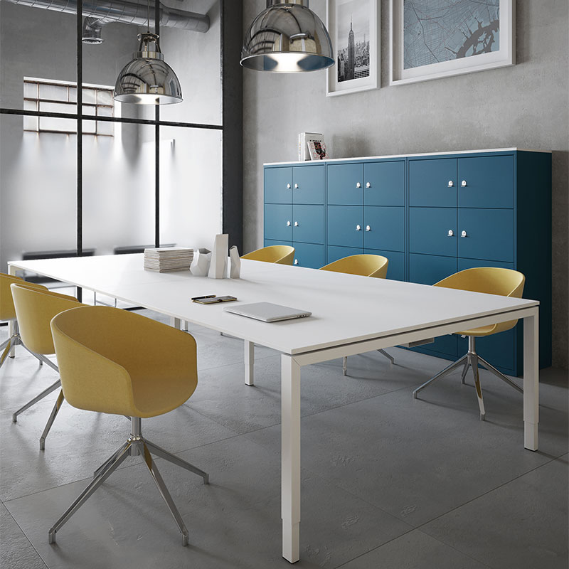 A wall of blue lockers behind a large white table with yellow chairs
