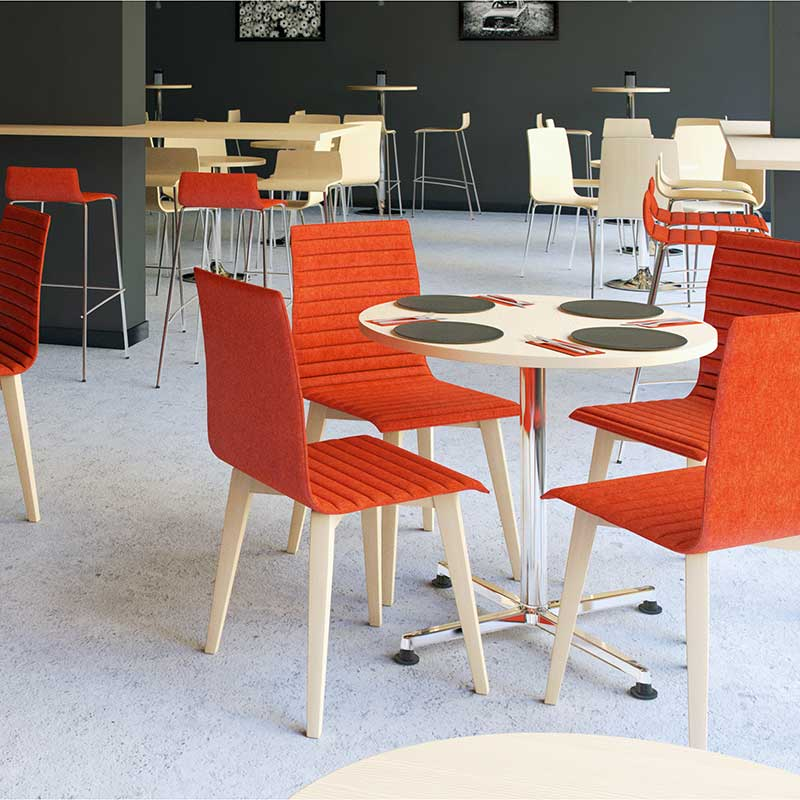 Cafe setting with red chairs around a circular wooden table