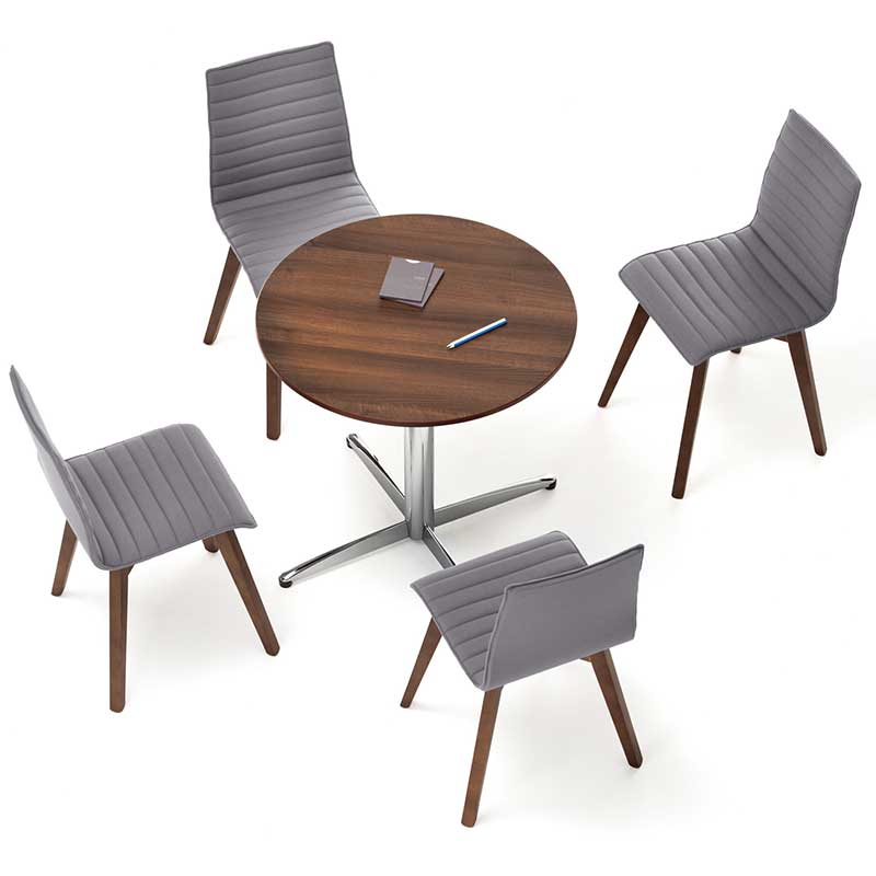 Overhead view of four grey chairs around a circular wooden table