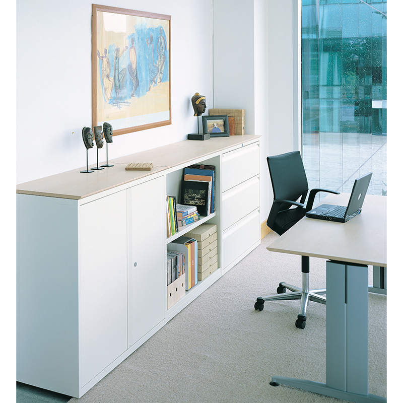 Office with white filing cabinet and storage, and a black chair next to a desk