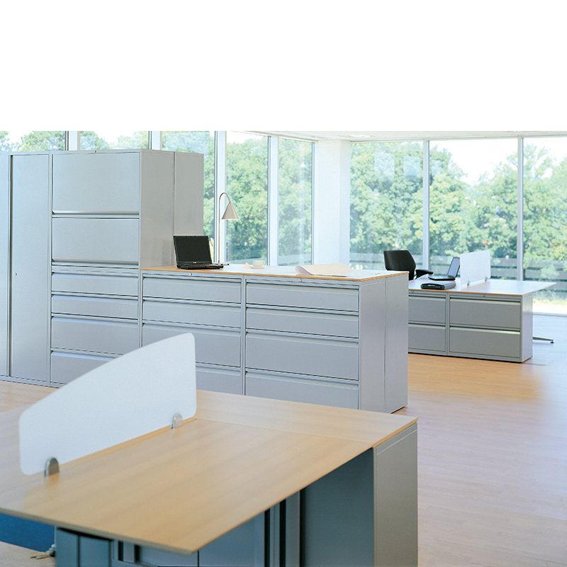White storage units in an office setting with desks and laptops